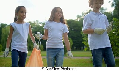 Cheerful little volunteers holding garbage bag and walking...