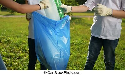 Charming kids working together while picking up garbage in...