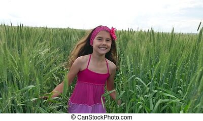 Girl teenager runs along a green field with wheat. Summer childhood happiness