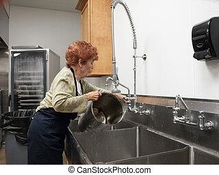 Senior Woman Washing Pot - Senior Woman washing large pot in...