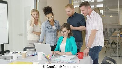 Woman with coworkers watching laptop - Young colleagues...