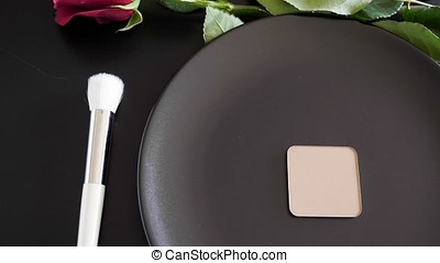 Makeup brushes in conceptual setup next to a black plate and...
