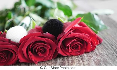 Makeup brushes on roses on wooden table - Beauty products....
