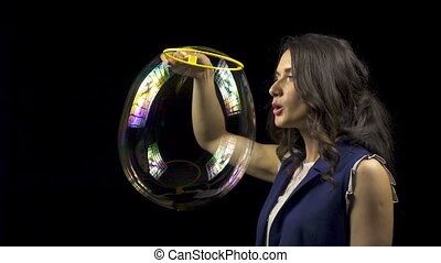 Beautiful woman blowing soap bubbles on black background