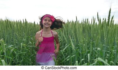 Girl teenager runs along a green field with wheat. Summer happiness childhood