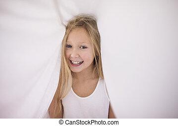 Cute girl sheltering under the duvet