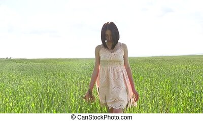 Close-up of a girl holding a wheat field. Green field of...
