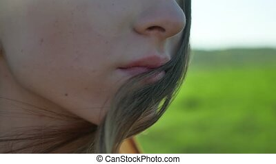 Girl lips. Girl is standing on the nature hair touch...