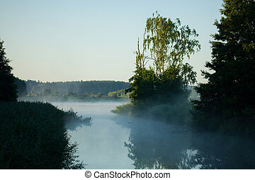 Lithuanian rural scenery in the morning - Misty lake during...