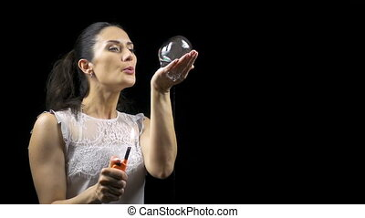 Brunette young woman making burning soap bubble on black...