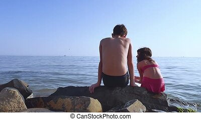 Boy and girl on the sea. A boy and girl are sitting on rocks...