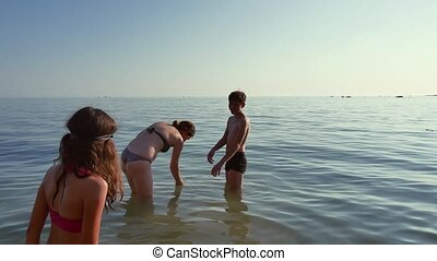 Family bathe in the sea. The boy stumbles in the water a...