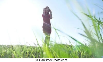 Girl wind nature. The girl is standing in the field of green grass. Woman freedom lifestyle