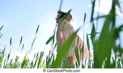 Girl in a dress in a field of green grass. Girl lifestyle...