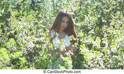 Girl and blooming cherry. The girl is lifestyle standing in...