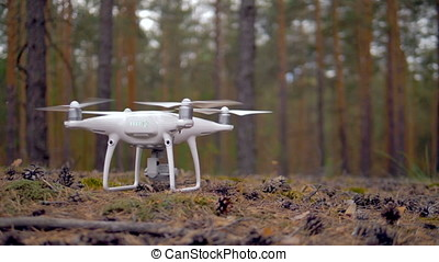 Slow motion epic shot of a drone takes off. - A quadrocopter...