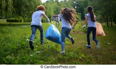 Children running to volunteers with trash bags with plastic...