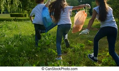 Little ecologists running and handing over garbage bags to...