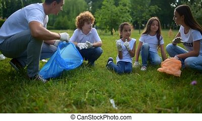 Experienced environmentalists chatting with children over...