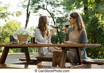 Amazing young two women sitting outdoors in park drinking...