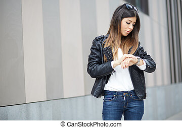 woman looking at her watch in urban street
