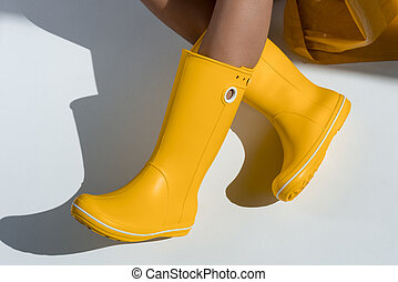 cropped view of woman wearing yellow rubber boots sitting on floor