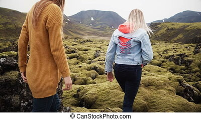Back view of two tourists woman hiking together in Iceland. Girls walking through the lava field covered moss.