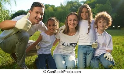 Friendly volunteers posing for camera and smiling -...