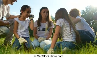 Millennial volunteers sitting on grass and joking with kids...