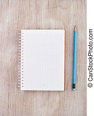 Notebook with pencil on desk - Top view of empty white...