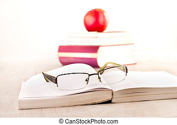 Eyeglasses on open book on table - Close up of reading...