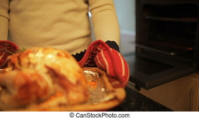 Cooking The Christmas Turkey - Mature man is checking the...