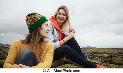 Two happy woman sitting on the lava field covered moss in Iceland and talking. Tourists friends resting after hiking.