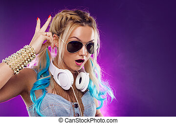 Young fashionable girl in disco style. Listening music and...