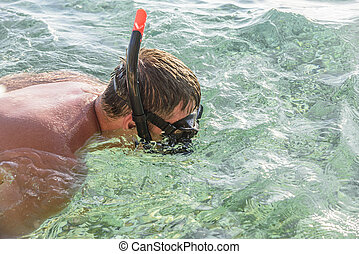 Man in a diving mask in sea water. - Man in a diving mask...