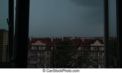 View from the window: sloping roofs of town houses in the thunderstorm and lightning