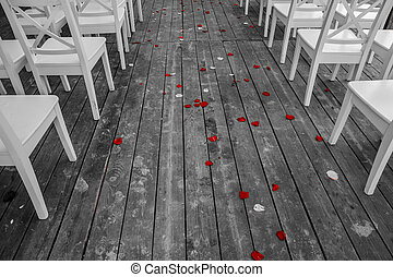 Wedding white chairs aisle with red rose petals on the wooden floor