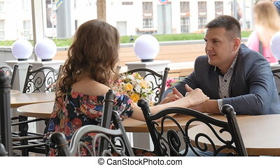Beautiful young couple on date. Sits at a table in a street cafe. Holding hands.