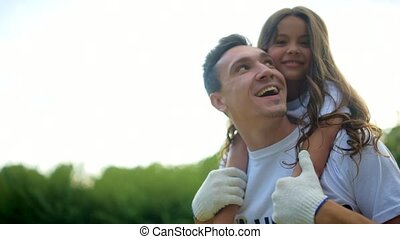 Beaming male volunteer holding charming girl on his back