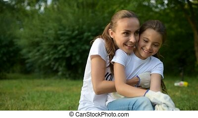 Smiling volunteer and girl embracing while sitting on grass...
