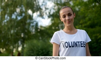 Charming female volunteer smiling for camera - Volunteering...