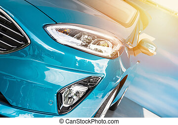 Front of a blue sport car in sunset