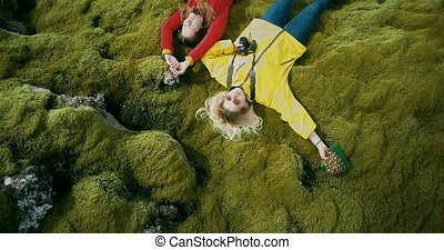 Aerial top view of the two happy woman lying on the soft...