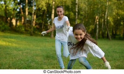 Extremely excited girl holding hand of volunteer and running...