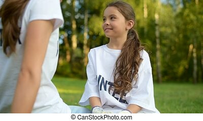 Radiant girl sitting on grass and talking to volunteer -...