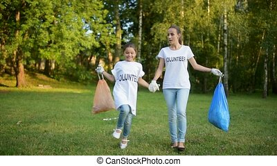 Radiant volunteers holding trash bags and walking around -...