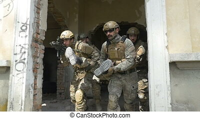Slow motion of special forces soldiers saving and carrying...