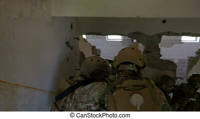 Teamwork of special military unit descending stairs during...