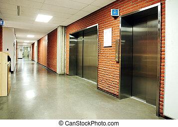 Steel door elevators in deserted hallway