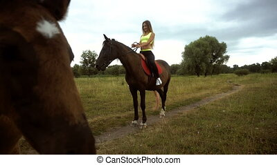 girl riding a horse and little foal looking into camera...